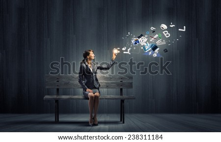 Young businesswoman holding mobile phone with flying out icons - stock photo