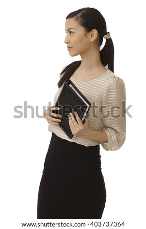 Young businesswoman holding personal organizer, looking right. - stock photo