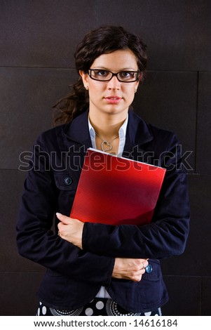 Young businesswoman holding red folder and posing for portrait on office corridor, looking at camera. - stock photo