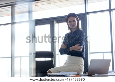 Young businesswoman holding smart phone while looking away at office- Corporate Business