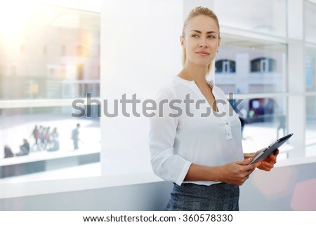 Young businesswoman holding touch pad and thinking about forthcoming meeting with important partners, female intelligent lawyer standing with digital tablet in modern office interior during work break - stock photo