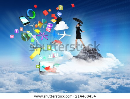 Young businesswoman holding umbrella against mountain peak through the clouds