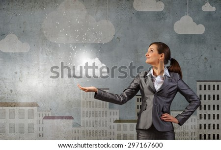 Young businesswoman holding white cloud in hands - stock photo