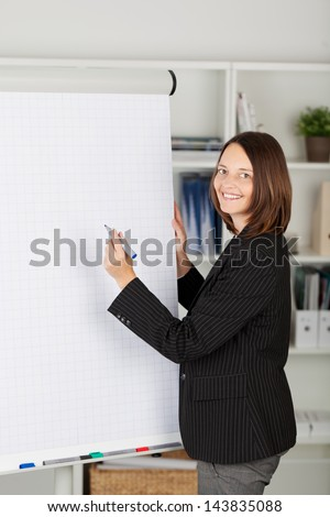 Young businesswoman in a black jacket writing on a blank flipchart with a marker pen during a presentation - stock photo