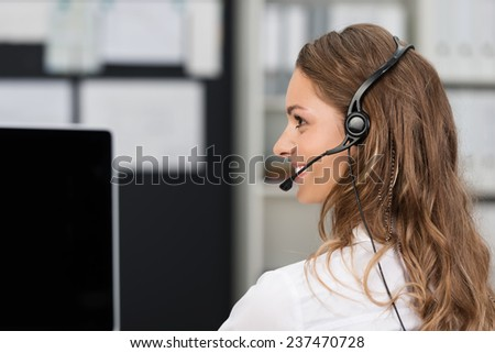 Young businesswoman in a call center or client services desk wearing a headset and smiling as she assists a customer - stock photo
