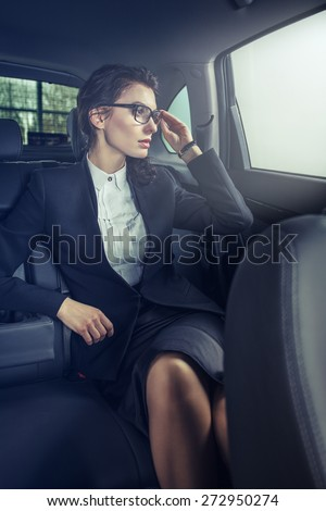 Young businesswoman in back seat of car - stock photo