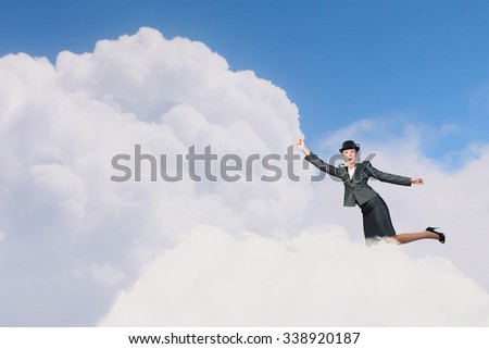 Young businesswoman in bowler hat on cloud