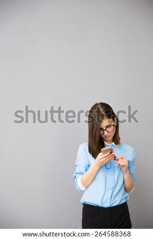 Young businesswoman in glasses using smartphone over gray background - stock photo