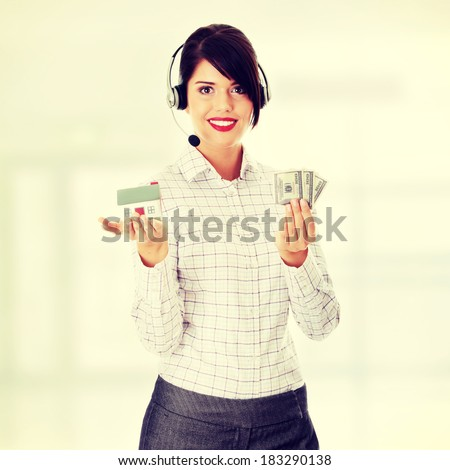 Young businesswoman in headset holding hose model and cash