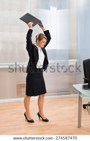 Young Businesswoman In Rage Throwing Laptop At Workplace - stock photo