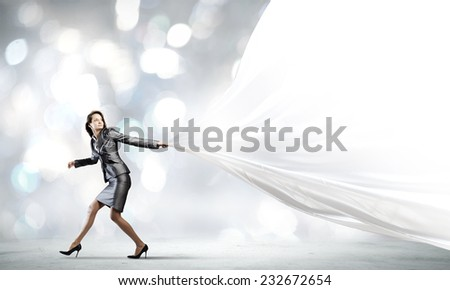 Young businesswoman in suit running against bokeh background - stock photo