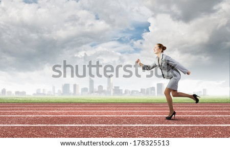 Young businesswoman in suit running on track