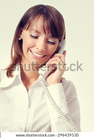 Young businesswoman in white business style clothing or support phone worker - stock photo