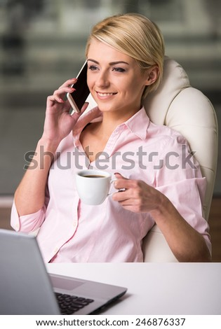 Young businesswoman is relaxing at office and talking by phone.