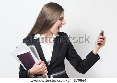 young businesswoman is shouting on the phone very angry in a white isolated background - stock photo