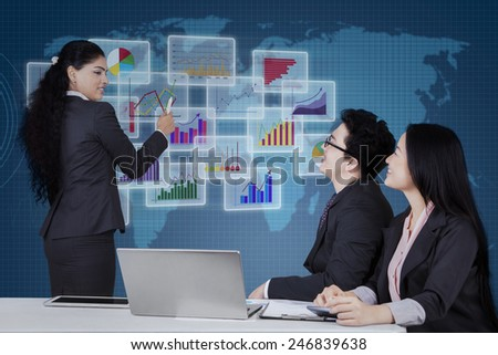 Young businesswoman leads business meeting and explaining financial chart on futuristic screen - stock photo