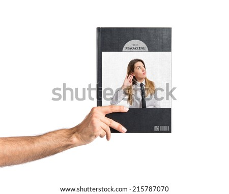 Young businesswoman listening printed on book - stock photo