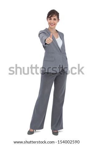 Young businesswoman looking at camera giving thumb up on white background - stock photo