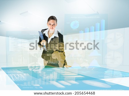 Young businesswoman looking at digital screen with diagrams and graphs - stock photo