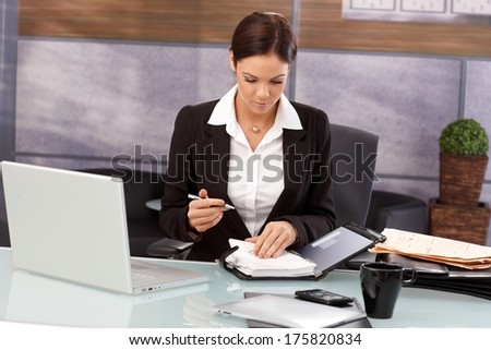 Young businesswoman looking at organizer, sitting at desk, working.