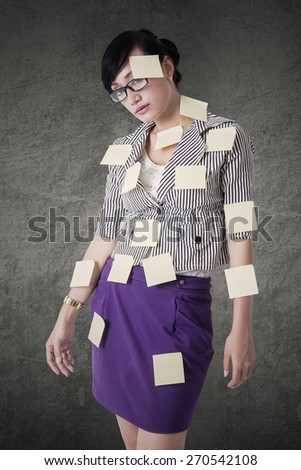 Young businesswoman looking at the camera with blank paper notes attached on her body - stock photo