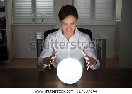 Young Businesswoman Looking Into The Future In A Crystal Ball In Office - stock photo