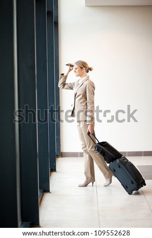 young businesswoman looking outside airport window - stock photo