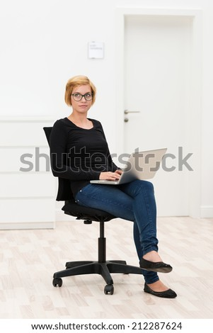 Young businesswoman lost in thought as she sits on an office chair in an empty room typing on her laptop which is balanced on her lap - stock photo