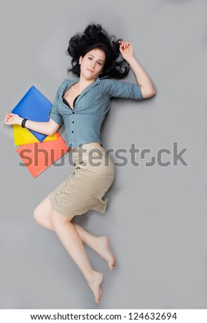Young businesswoman lying on the floor and looking at camera