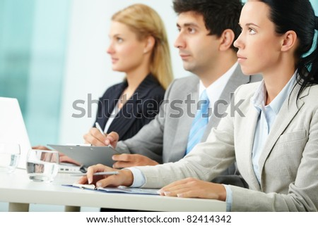 Young businesswoman making notes at conference with her colleagues on background