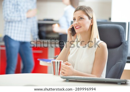 Young businesswoman on a coffee break in the office talking on the phone - stock photo