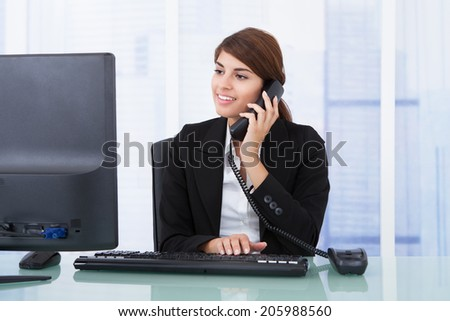 Young businesswoman on call while using computer at desk in office