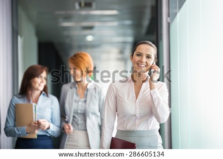 Young businesswoman on call with colleagues in background at office corridor - stock photo