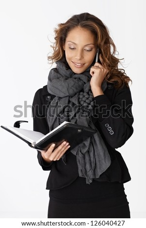 Young businesswoman on mobilephone, looking at personal organizer.
