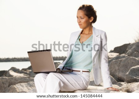 Young businesswoman on the beach with laptop - stock photo