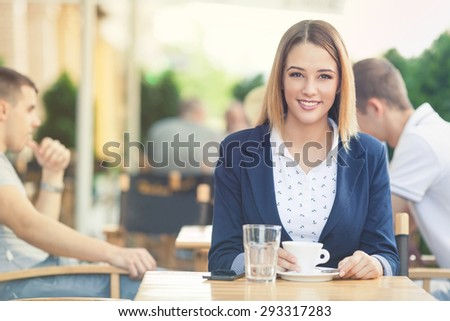 Young businesswoman on the coffee break in a cafe
