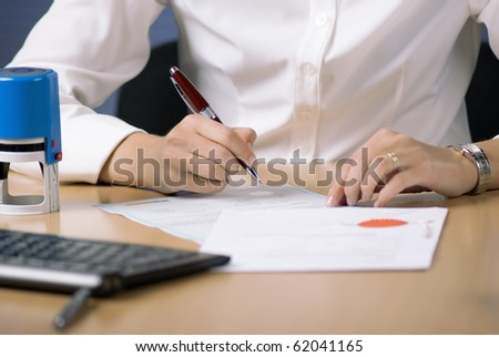 Young businesswoman (or notary public) sitting at the desk in office and signing document - stock photo