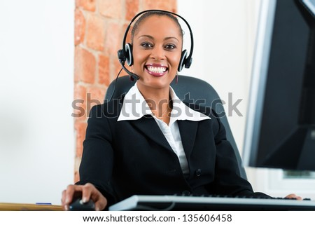 Young businesswoman or secretary working in her Office, she is sitting on the desk in front of the window and working on a computer with a headset, she has a customer pitch - stock photo