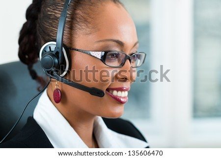 Young businesswoman or secretary working in her Office with a headset, she has a customer pitch - stock photo