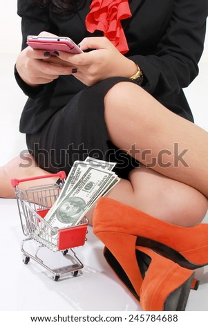 Young businesswoman playing phone with shoes and a lot of money in shopping cart, isolated on white background - stock photo