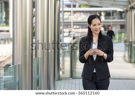 Young businesswoman portrait using smartphone in Hong Kong.