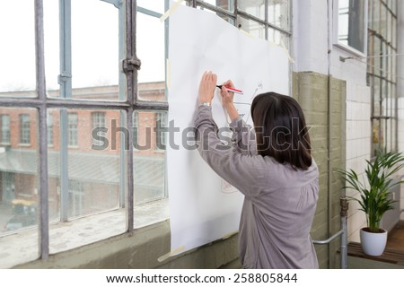 Young businesswoman preparing a presentation or team meeting writing on a white screen suspended in a window - stock photo