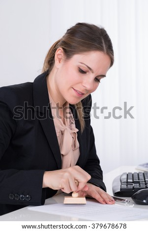Young Businesswoman Pressing Wooden Stamp On Paper At Desk - stock photo