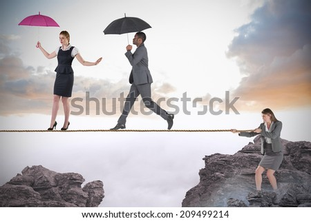 Young businesswoman pulling a tightrope for business people against rocky landscape - stock photo