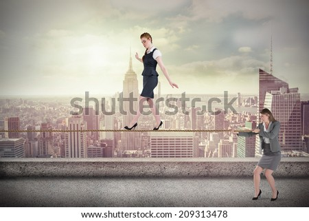 Young businesswoman pulling a tightrope for business woman against balcony overlooking city - stock photo
