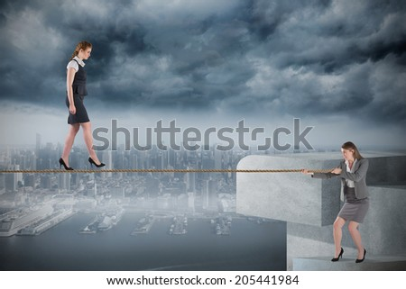 Young businesswoman pulling a tightrope for business woman against coastline and city - stock photo