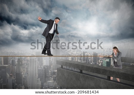 Young businesswoman pulling a tightrope for businessman against balcony overlooking city - stock photo