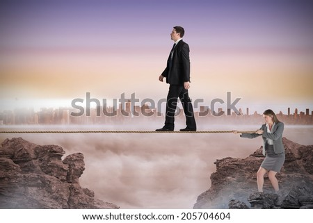Young businesswoman pulling a tightrope for businessman against cityscape on the horizon - stock photo