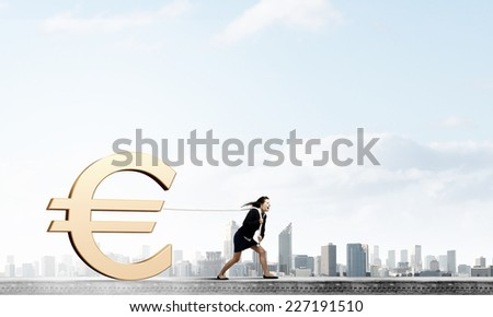 Young businesswoman pulling euro sign with rope - stock photo