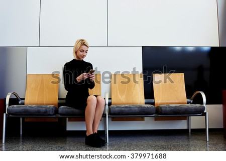 Young businesswoman reading news on mobile phone while sitting in waiting room after meeting with client, charming female dressed in black dress chatting on cell telephone during work break in hallway - stock photo